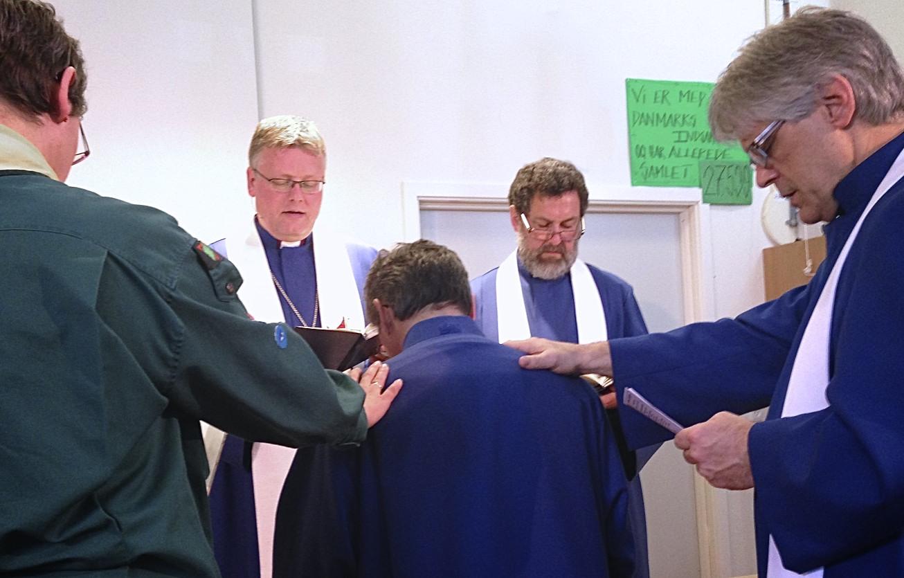 Dean Andersen ordineres af biskop Christian Alsted, distriktsforstanderne Keld Munk og Jørgen Thaarup. Desuden lægger hans valgte fadder Pastor Mark Lewis og en leder fra hans lokale menighed, Bettina Pedersen også hænderne på ham.